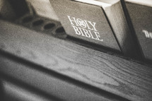 Bible in the back of a church pew.