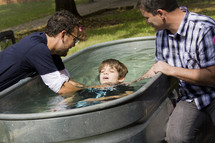 a child being baptized in a trough