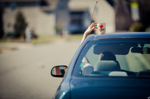 driver reaching for cup on car roof, driving away in a rush in the suburb