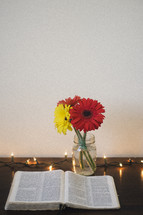 gerber daisies in a mason jar and an open Bible