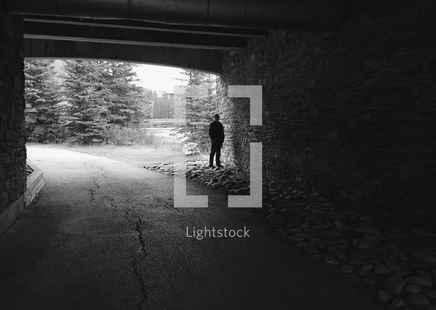 an iPhone capture of a man's silhouette under a dark bridge