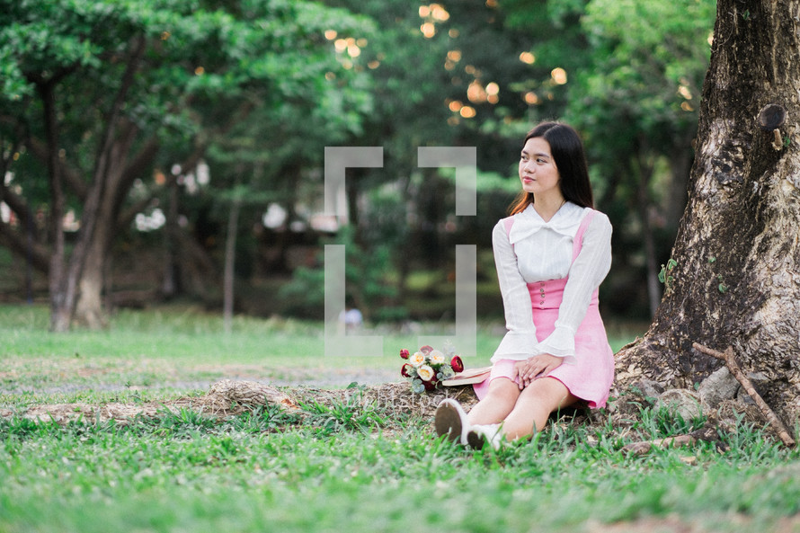 a woman sitting in the grass with a bouquet of flowers lap