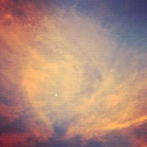 moon behind pink and white wispy clouds