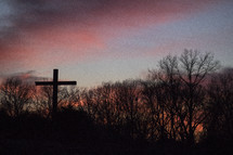 cross under a pink sky at sunset