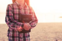 young girl holding holy bible, standing on the beach at sunset