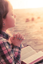 young girl praying on the beach with her bible in her lap at sunset; thinking, hearing from God