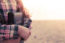 young girl standing on the beach holding her bible at sunset