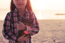 young girl happy, smiling, standing on the beach holding her bible at sunset