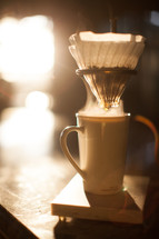 slow brew coffee filter and coffee mug in morning sunlight