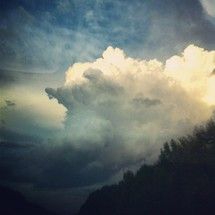 Sun shining behind cloud formation in stormy sky over tree tops.
