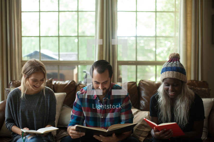 man and women reading Bibles at a fall Bible study