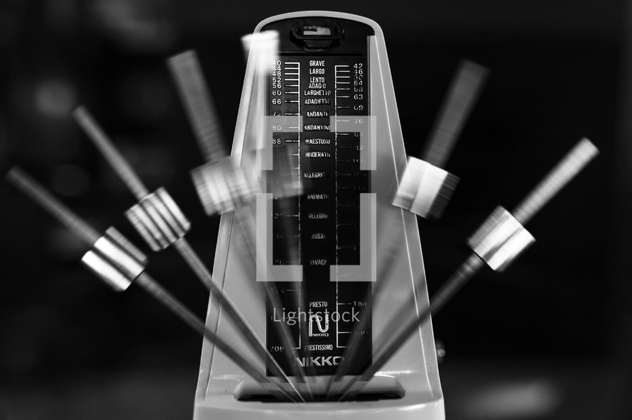 Metronome in motion, in black-and-white.