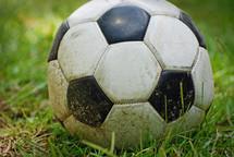 dirty soccer ball in grass