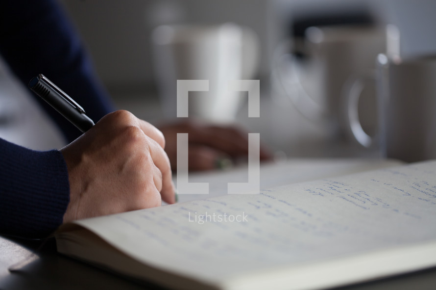 woman writing in a notebook at work