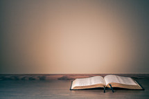 Open bible on a table against a wall