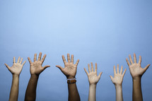 raised hands against a blue background