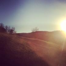 sunburst over rolling hills
