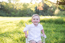 a child sitting in a chair in the grass