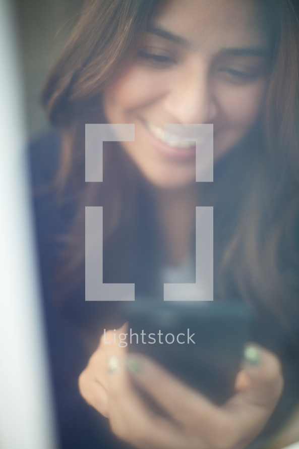 a smiling woman looking at a cellphone screen