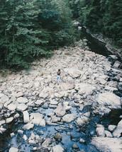 woman walking on rocks along a stream