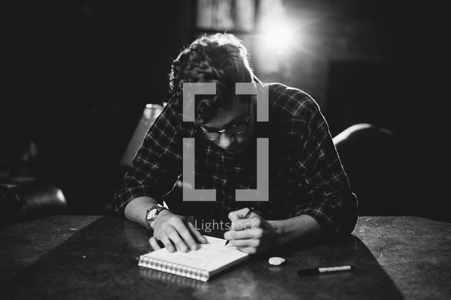 man writing in a notebook