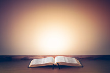 open bible on a table against a bright and colorful wall