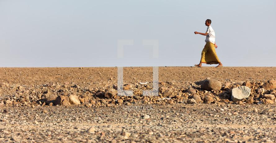 man walking across a desert in Ethiopia
