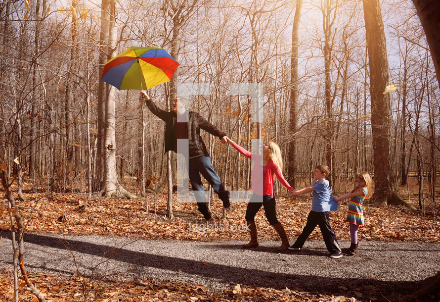A family lifting off the ground holding an umbrella