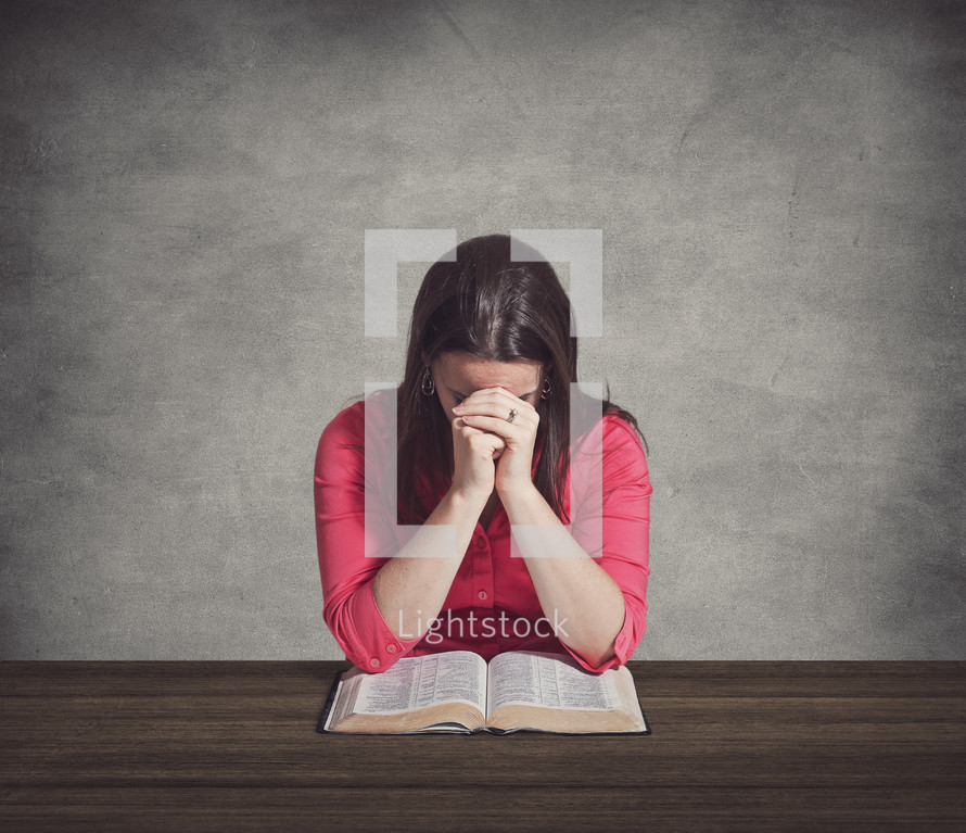 Woman praying over a Bible on a wooden table.
