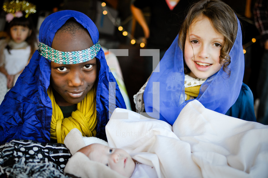 children dressed as Mary, Joseph, and baby Jesus in a live nativity scene