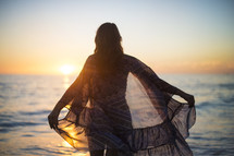 a woman in a sheer shirt standing in front of the ocean at sunset