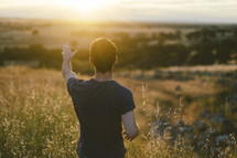 young man with a raised hand standing in a field at sunset