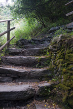 Stone steps with a wooden railing next to a moss covered rock wall.