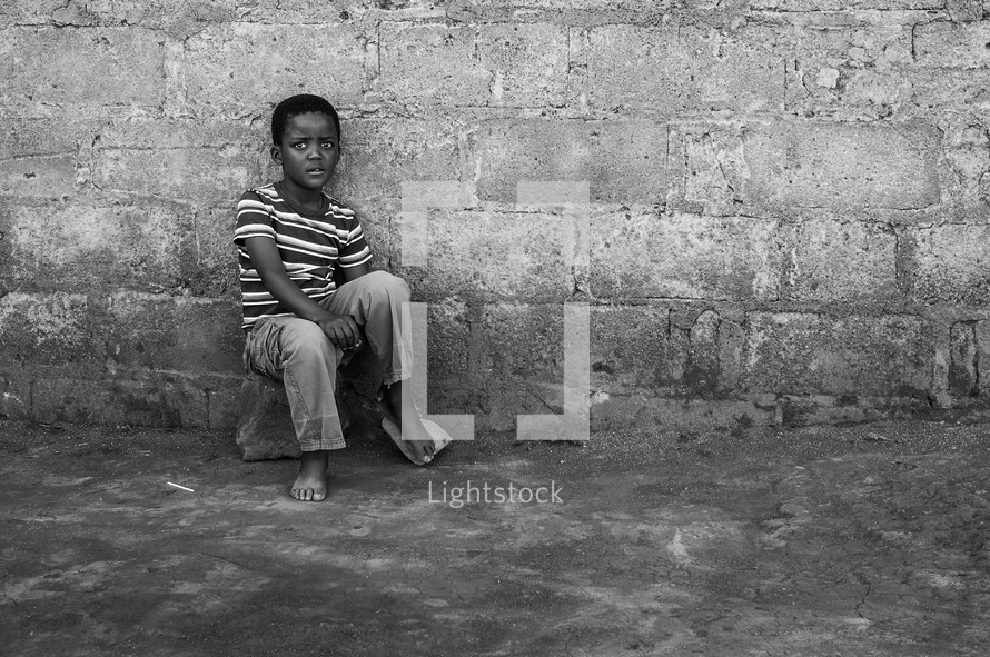 a shy little boy sitting on a rock in front of a wall outdoors