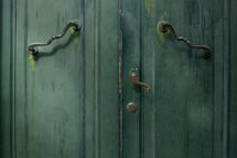 Cabinet hardware on green doors.