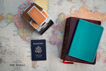 A passport, bible, notebook and a polaroid camera over an old world map.