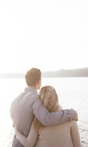 couple standing together in front of a lake
