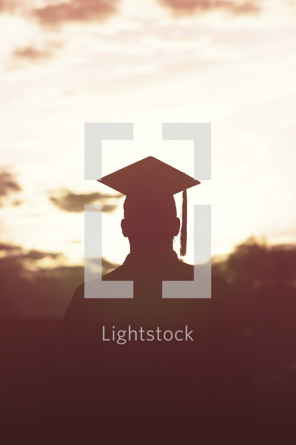silhouettes of graduate in cap and gown.