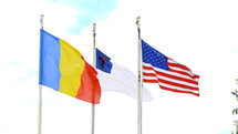 Romanian, American, and Christian flags on flag poles