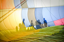 Onlookers cast shadows on the side of a hot air balloon.