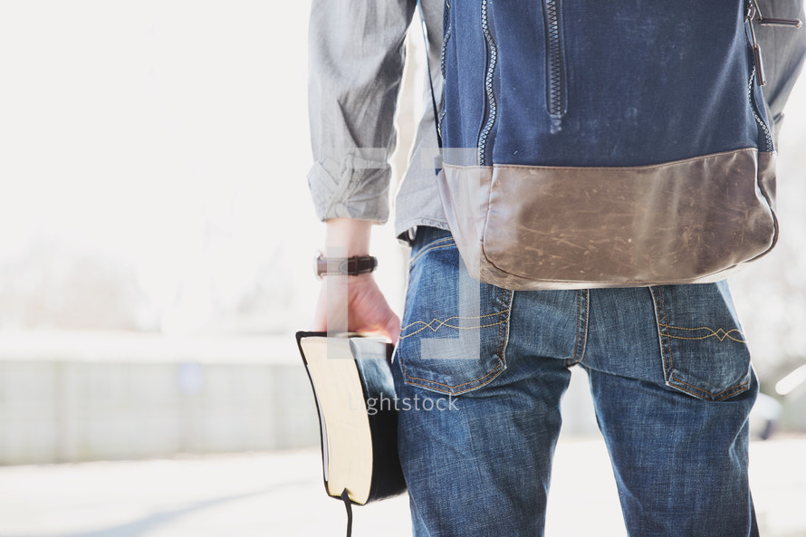 college student holding a Bible at his side