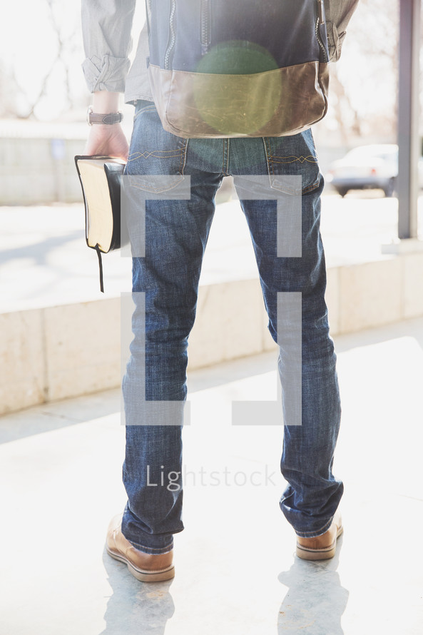 man with a backpack holding a Bible at his side