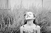 A little girl turns her face toward the heavens.