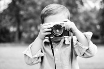 A little boy photographs the photographer with a vintage toy camera.