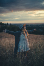 a woman with outstretched arms standing in a field