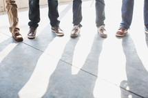 feet of men standing on a sidewalk