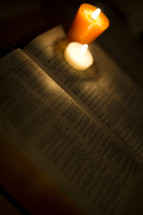 Open Bible with two votive candles on corner of pages.