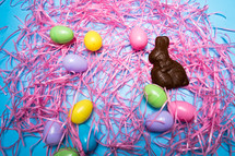Chocolate Easter rabbit and Easter eggs over a blue background