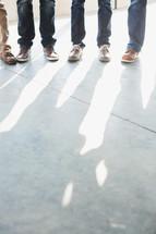 feet of men standing on a sidewalk