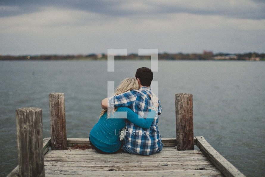 Embraced couple sitting on a wooden pier.
